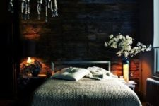 04 a moody bedroom with a weathered wooden wall and a boho bead chandelier is very welcoming