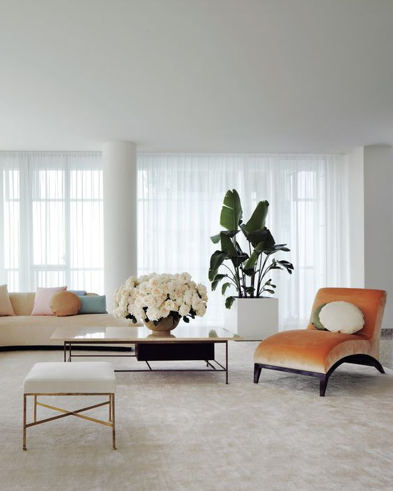 a peachy curved velvet lounger adds color and brings chic to the neutral space