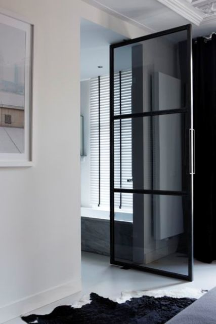 a smoked glass door with window panes is a cool idea to separate your en-suite bathroom from the bedroom