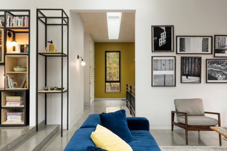 Bold touches like this blue sofa and yellow pillows add interest to the space
