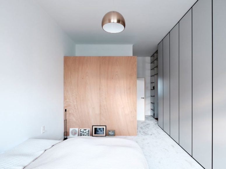 The bedroom is decorated in neutrals, with a wooden space divider and closed storage units