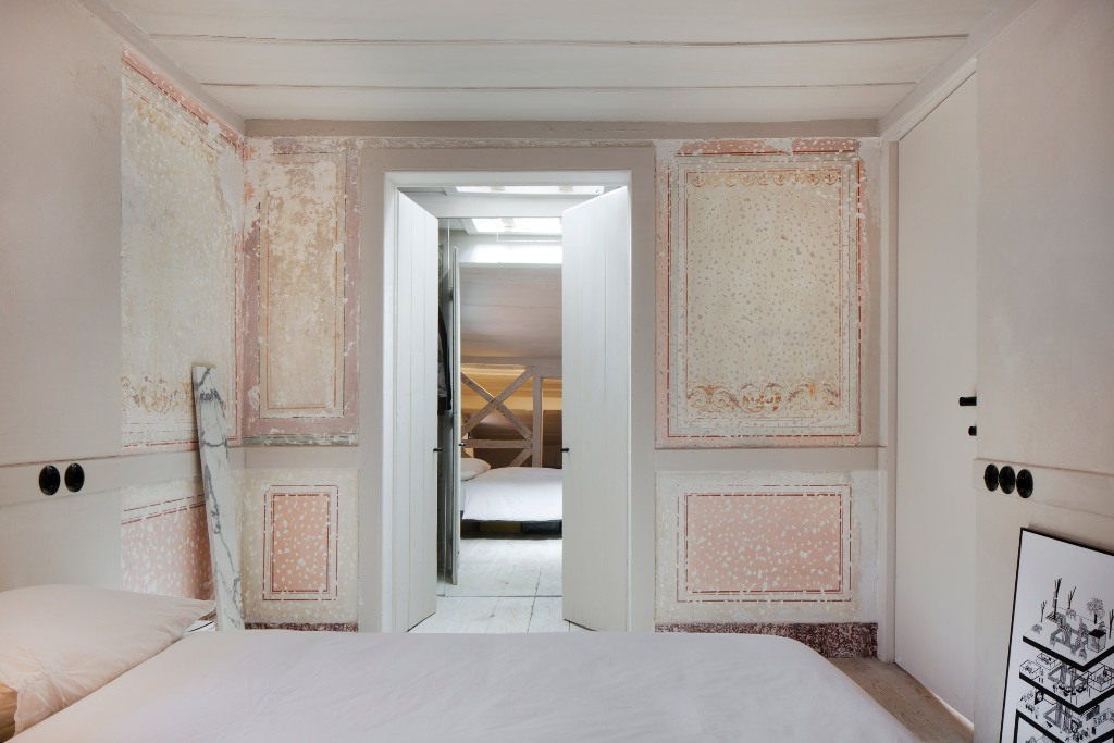 The bedroom is done in all neutrals, there's a large bed and some original frescoes that make a statement