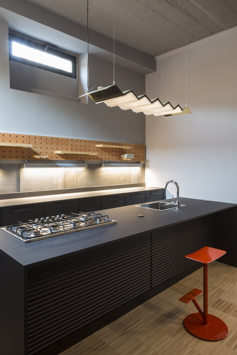 The kitchen is done with black metal cabinets, a pegboard with various shelves attached and a pendant lamp