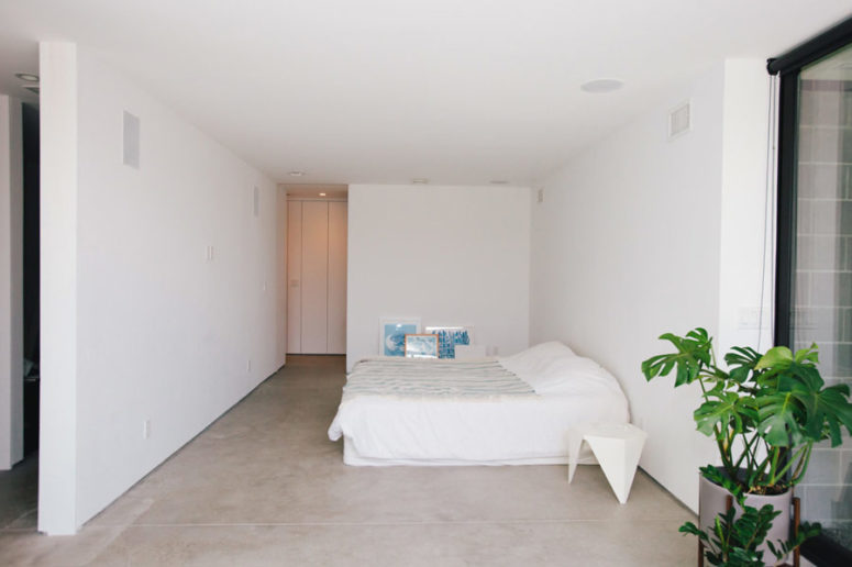 The master bedroom is all-white, with a large bed and some blue artworks plus potted plants