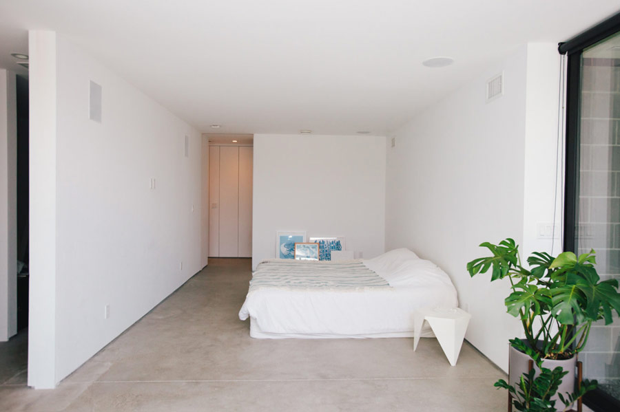 The master bedroom is all white, with a large bed and some blue artworks plus potted plants