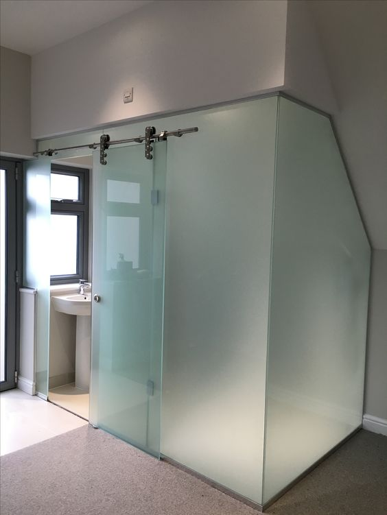 a bathroom cubicle clad with frosted glass and with a main sliding door is a bold idea for a modern space
