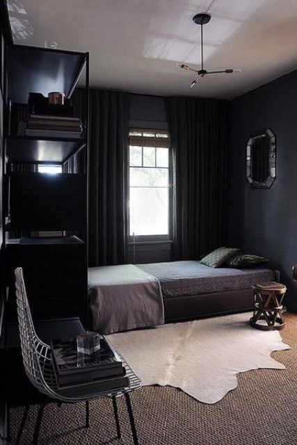 a comfy moody bedroom with layered rugs, thick curtains and dark bedding for winter