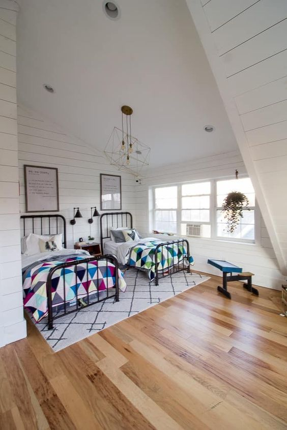 a cozy and large attic bedroomwith two beds and colorful textiles plus geometric ceiling lamps
