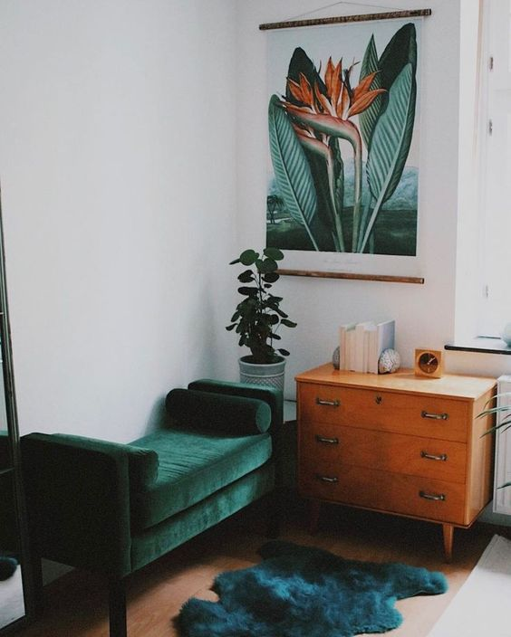 a dark green velvet bench and a darker green rug make up a chic and colorful nook