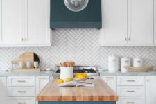 05 a white kitchen with a herringbone tile backsplash and a navy hood and kitchen island with a wooden countertop