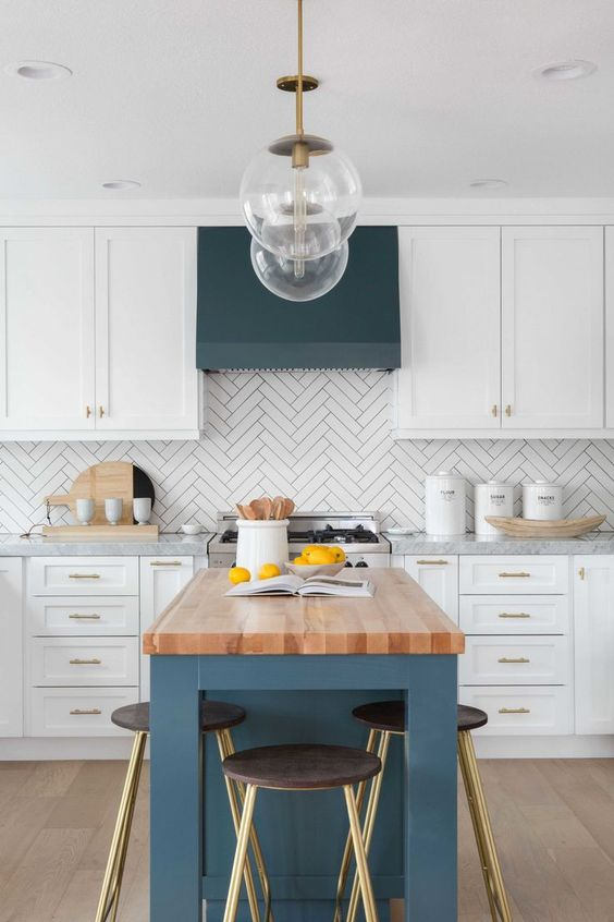 a white kitchen with a herringbone tile backsplash and a navy hood and kitchen island with a wooden countertop