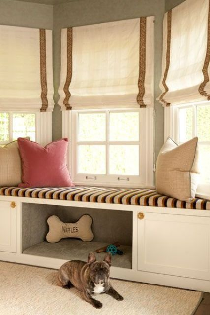 an upholstered windowsill bench with some built-in storage and a comfy pet niche with toys