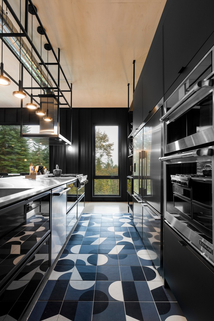 A moody kitchen is done with black sleek cabinets, a mosaic tile floor in black and white