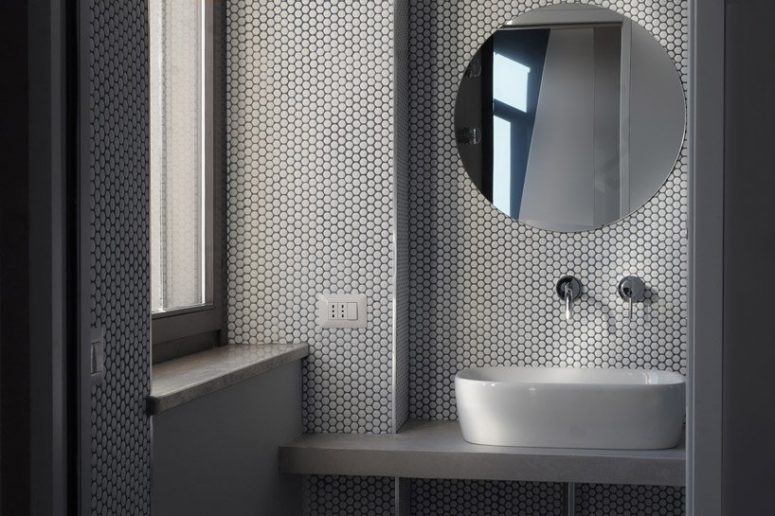 The bathroom is clad with white penny tiles, there's an oval sink and a round mirror