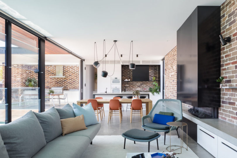 The dining space with chaotically suspended lamps over it separates the kitchen from the living room