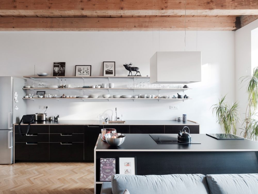 The kitchen is done with black sleek cabinets and a white vent for a contrasting look