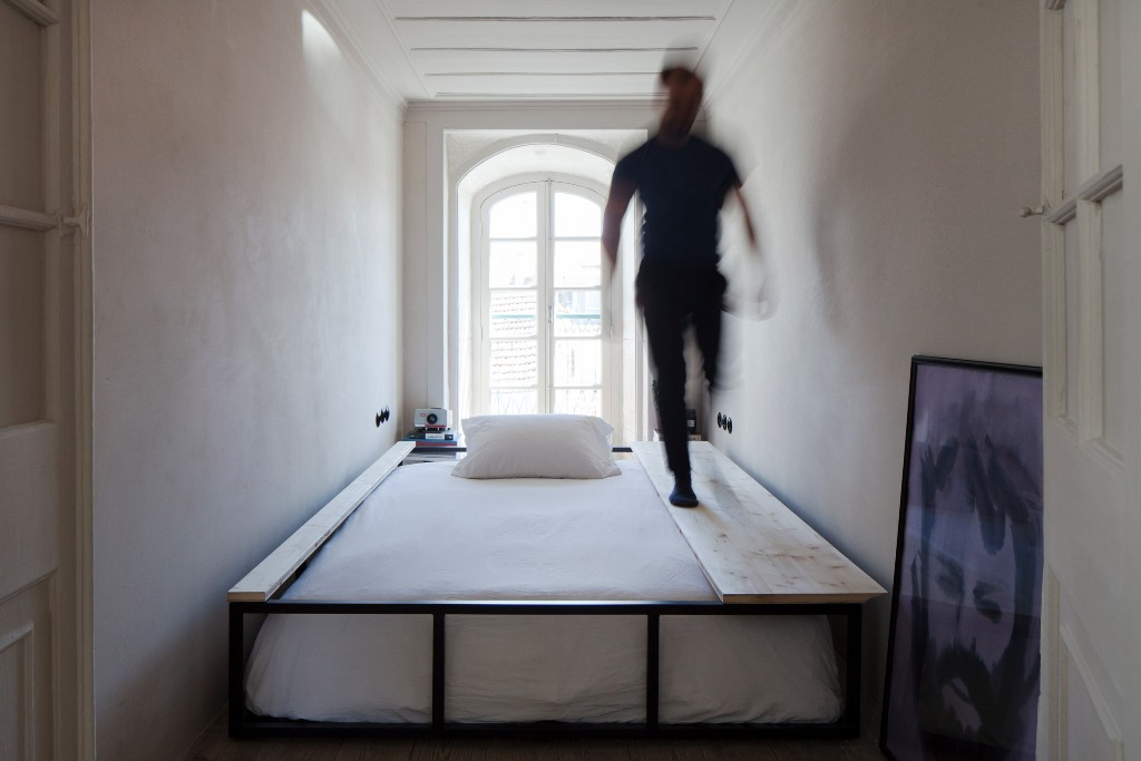 The second bedroom shows off a bed that can be easily covered and turned into a sitting space