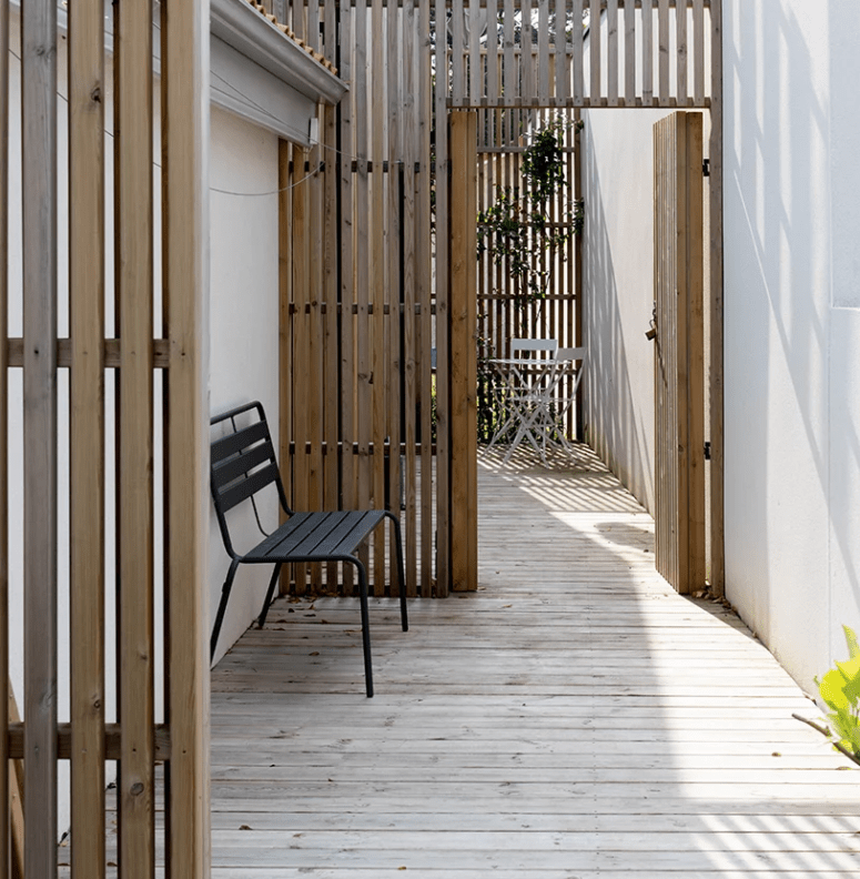There is an outdoor deck with some spaces divided with pine screens to unify the look from outdoors