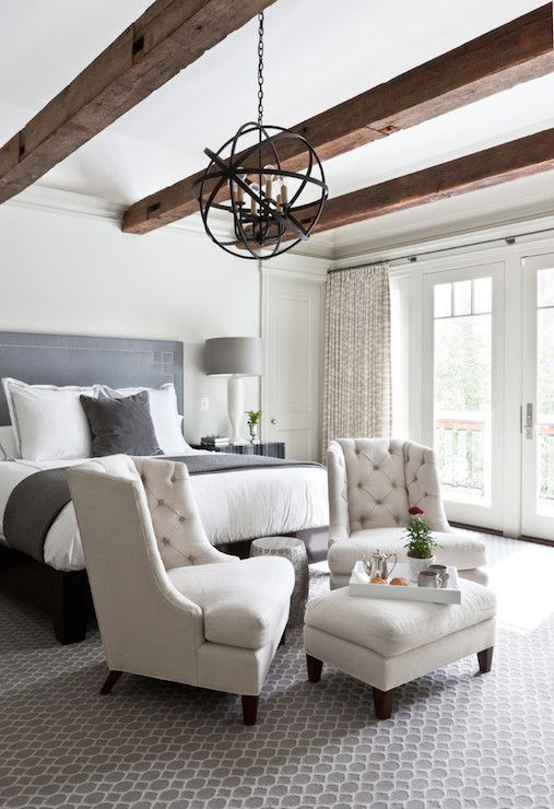 a couple of upholstered chairs and an ottoman by the foot of the bed is a simple idea