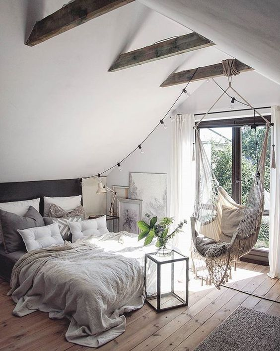 a cozy neutral bedroom with much light, stained beams on the ceiling and mcuh texture thanks to textiles