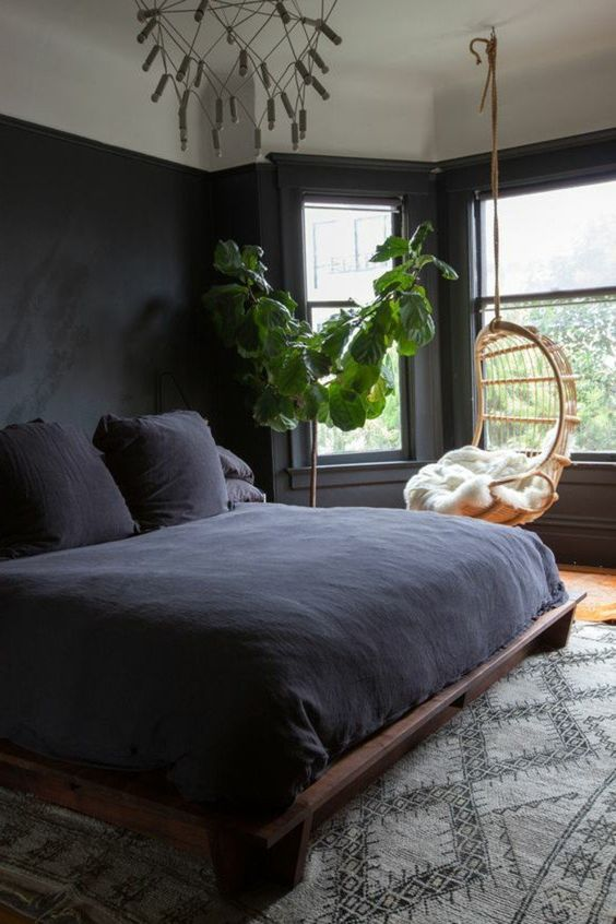 a dark bedroom is filled with natural light, styled with dark bedding and neutral textiles