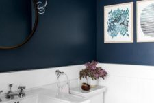 06 the bathroom features a contrasting look of a navy walls and white appliances and tiles