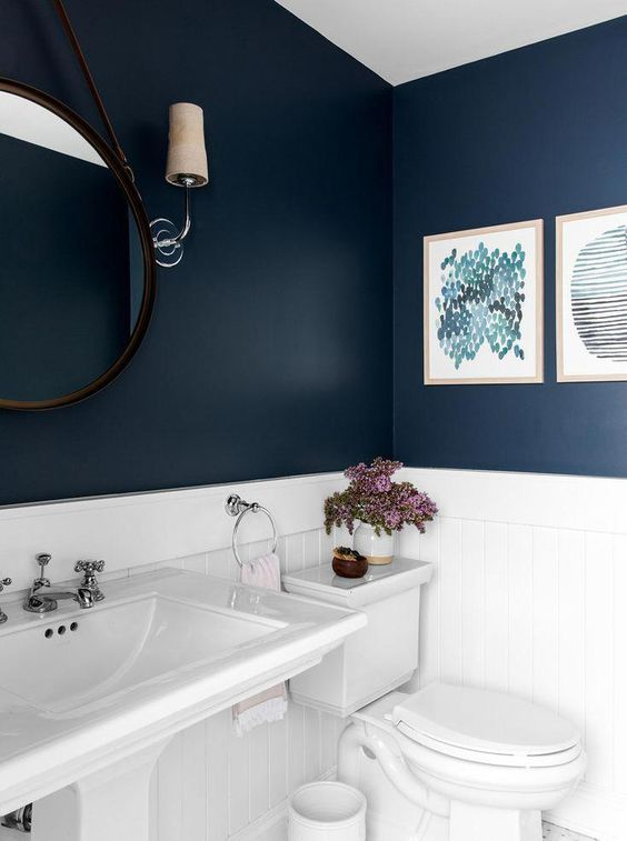 the bathroom features a contrasting look of a navy walls and white appliances and tiles
