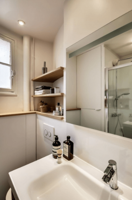 The bathroom is done with matte neutral panels and touches of natural wood, just like the kitchen