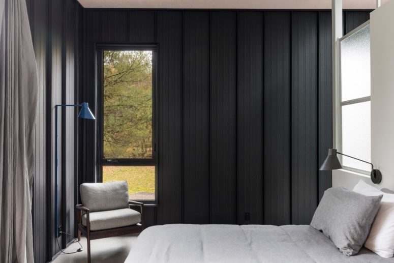 The bedroom also features black wood clad walls, windows fill the space with natural light