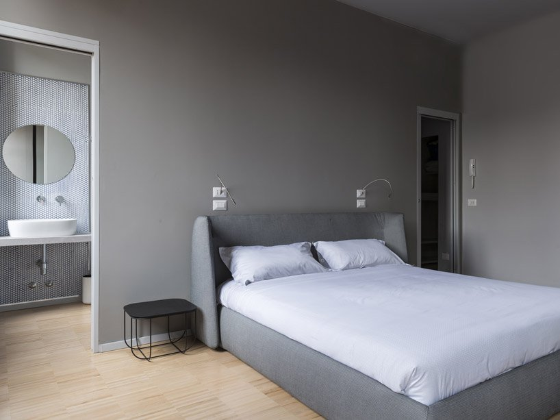 The bedroom is done in the shades of grey, with grey walls and a grey upholstered bed and a duo of metal bedside tables