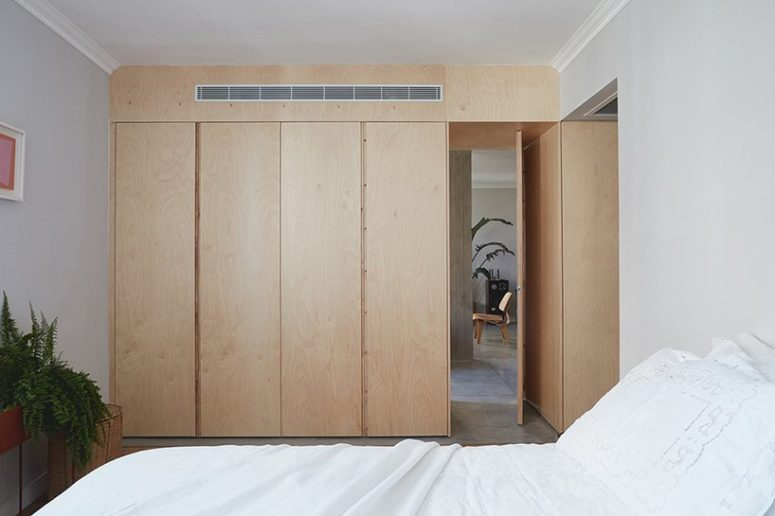 The master bedroom is very laconic and neutral, with a large plywood wardrobe and a comfy bed