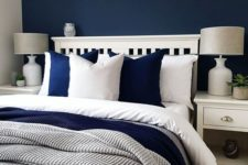 07 a cozy bedroom done in navy, white and greys looks contrasting, bold yet very inviting