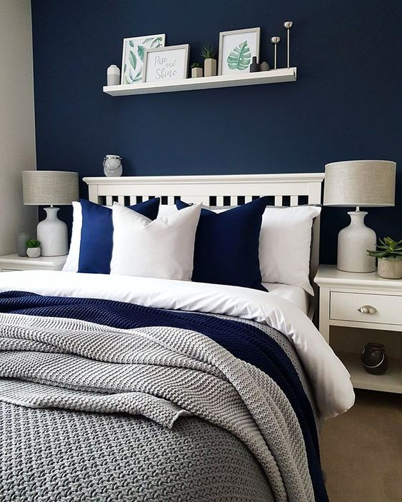 a cozy bedroom done in navy, white and greys looks contrasting, bold yet very inviting