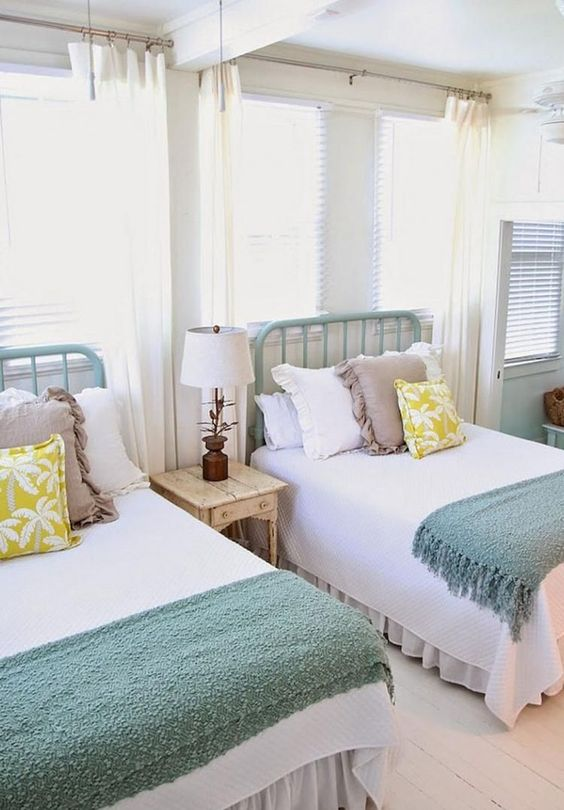 a cozy farmhouse twin guest bedroom with mint-painted beds and large windows