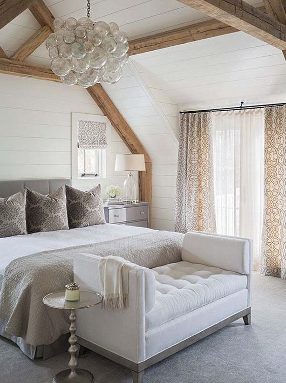 a creamy tufted bench at the foot of the bed is a stylish idea for a neutral sleeping space