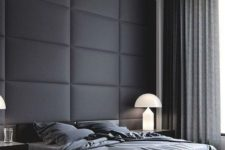 07 a minimalist neutral bedroom with a black upholstered statement wall and dark bedding looks very comfy