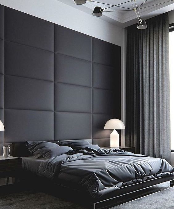 a minimalist neutral bedroom with a black upholstered statement wall and dark bedding looks very comfy