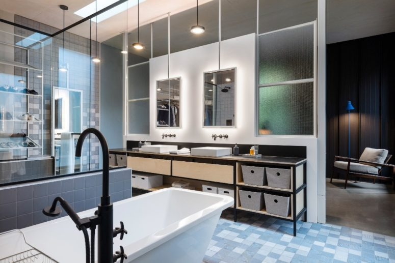 The bathroom is a spacious room with much light, blue tones and many mirrors