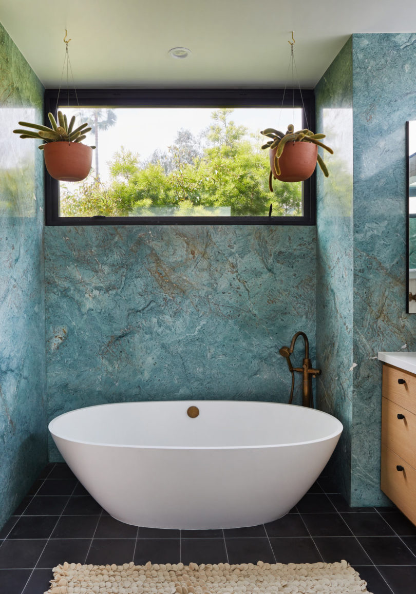 The bathroom is done with black tiles on the floor and blue Carrara stone that really impresses
