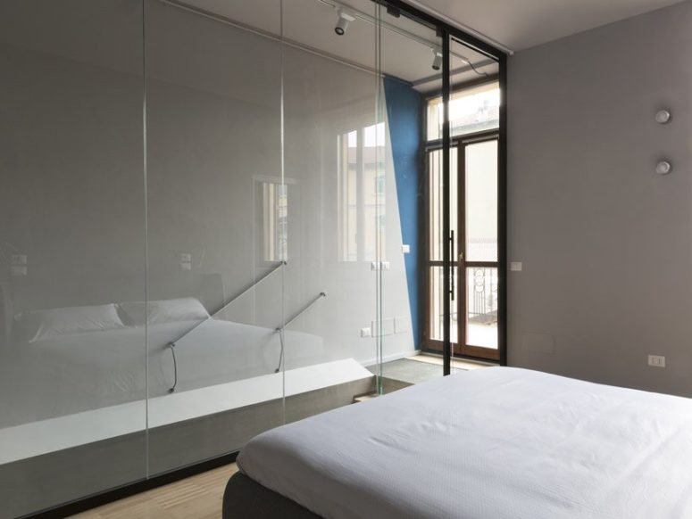 The bedroom is separated from the stairs with large sheets of glass