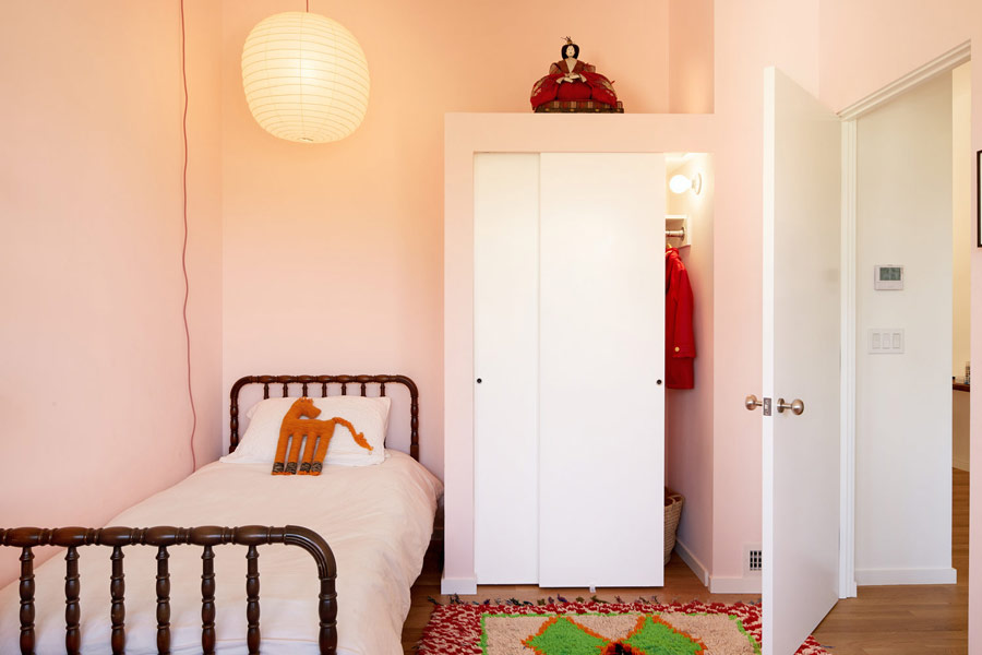 The kids' space is done in pink, with a comfy wooden bed, a colorful rug and much light to make it welcoming