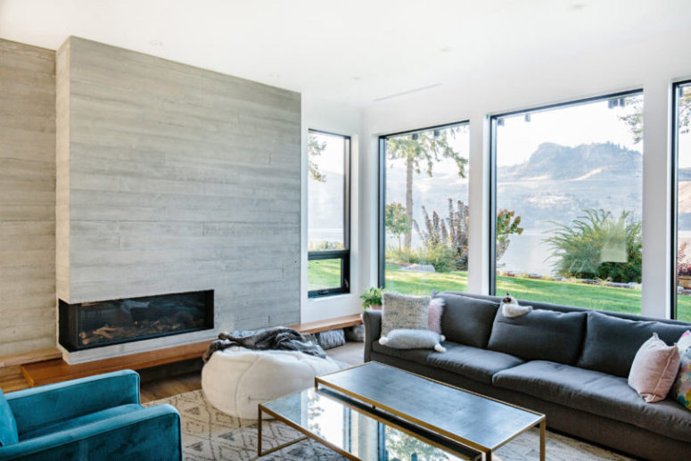 The living room is done with much glazing, a built-in fireplace and lots of colorful furniture