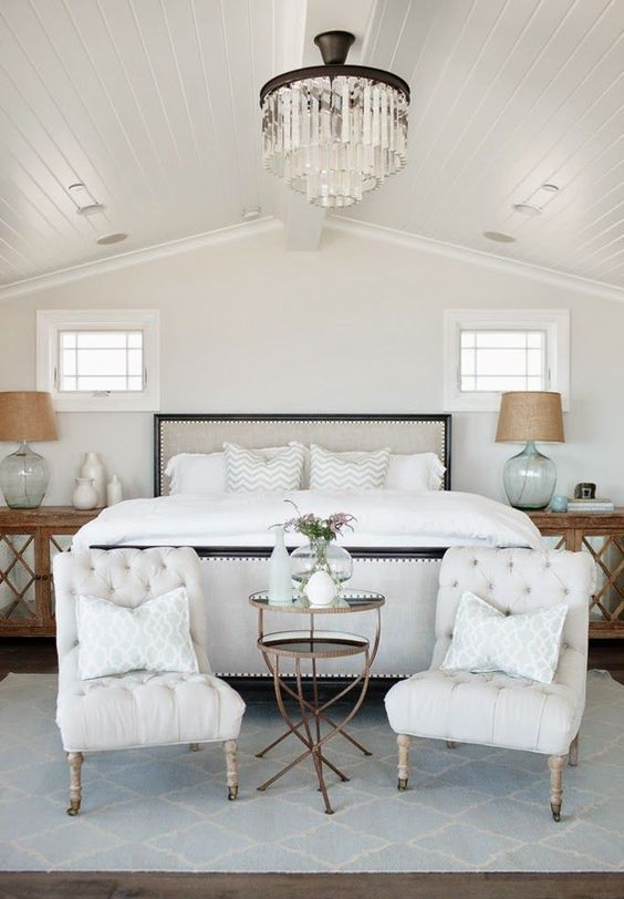 a duo of elegant tufted chairs at the foot of the bed is a stylish and comfy option to rock in a bedroom