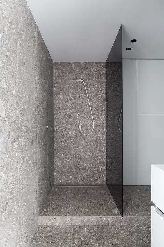 a modern grey bathroom clad with terrazzo and a smoked glass shower door for privacy