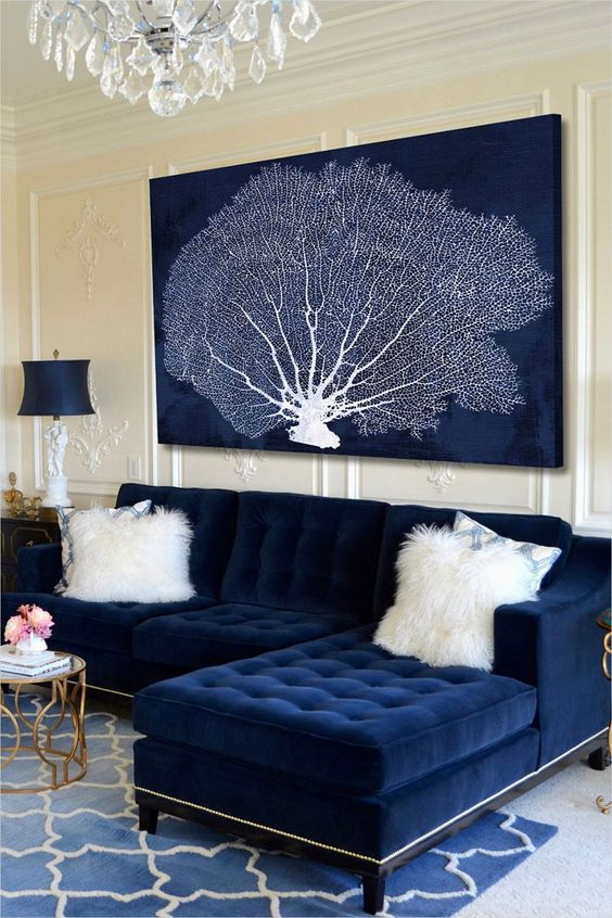 a nautical space with a navy tufted couch and a large artwork in navy and white showing off a coral