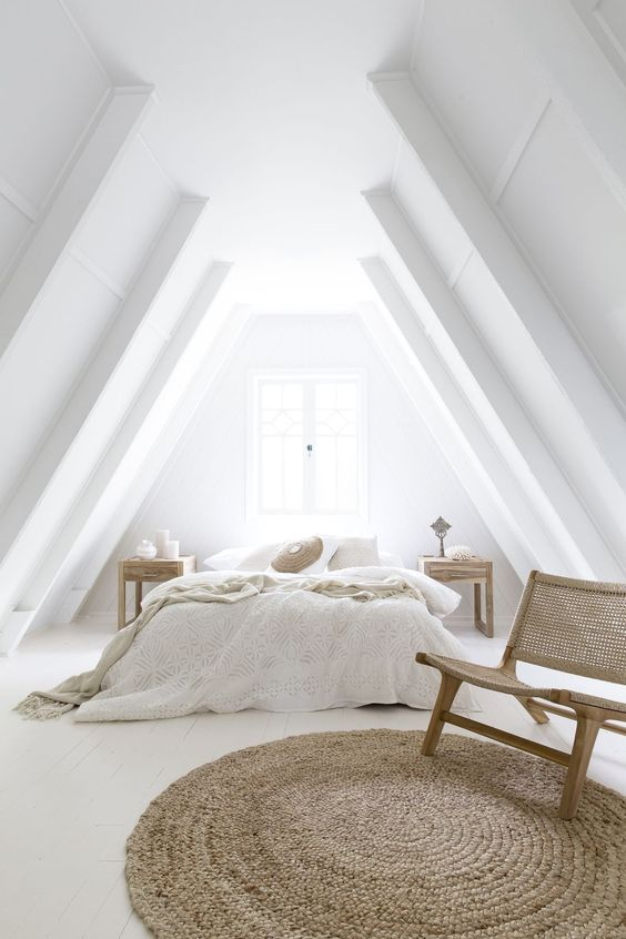 a totally white attic bedroom with wood and wicker touches that make it very cozy