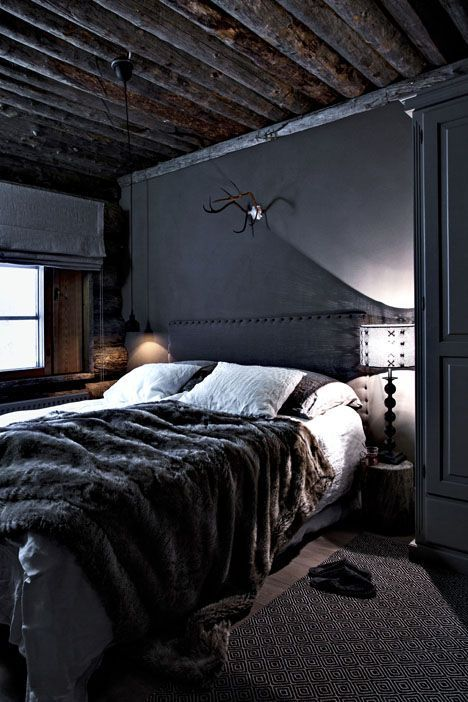 a welcoming dark cabin bedroom with a wooden ceiling and a faux fur throw plus wooden touches