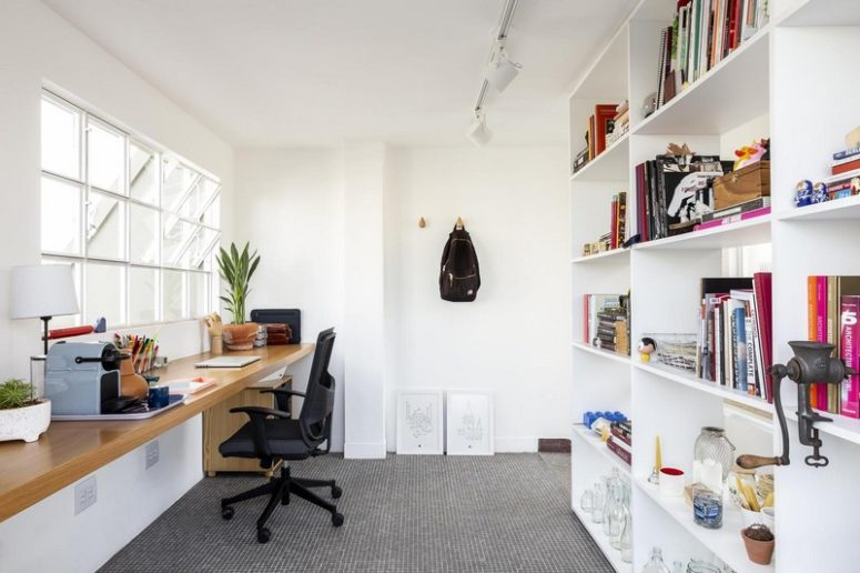 A home office is done with a large storage unit and a floating desk by the window, potted greenery refreshes the space