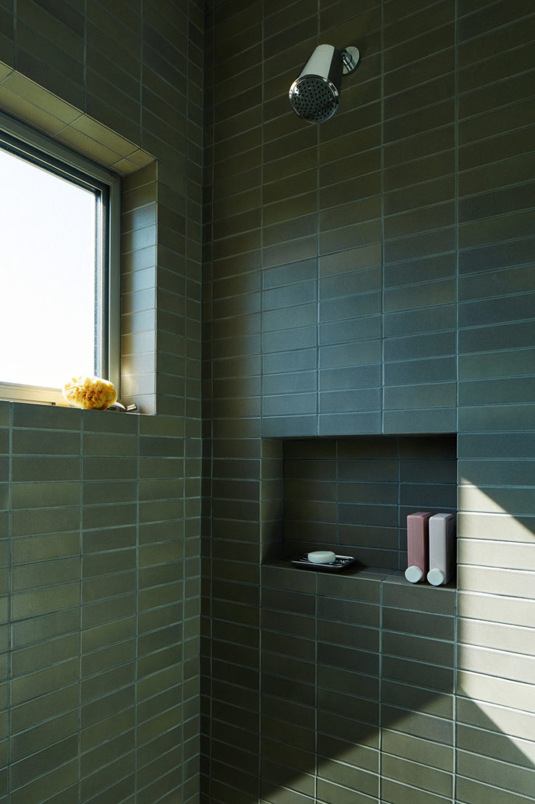 The bathroom features a shower with matte dark green tiles that are long and narrow