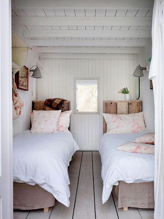a cozy vintage inspired guest bedroom with twin beds and wooden floors, walls and a ceiling